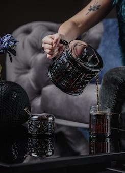 暗い壁の側面図でカップにブラックティーポットからお茶を注ぐ女性