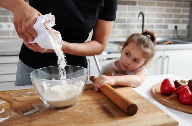 紙の包装から透明なガラスのボウルに白い小麦粉を注ぐ女性。彼女の隣に彼女の小さな娘が座って、料理の過程を見守っています。