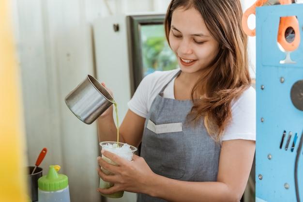 Женщина наливает напиток в пластиковый стакан, наполненный льдом