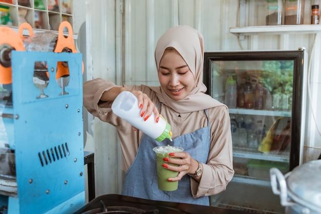 Женщина наливает молоко в напиток