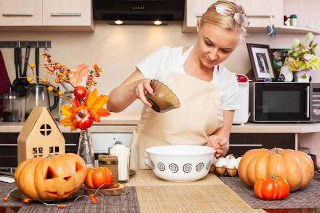 秋の装飾が施されたキッチンで、ハロウィーンのクッキー生地に砂糖を注ぐ女性。ハロウィン用のクッキー作り。