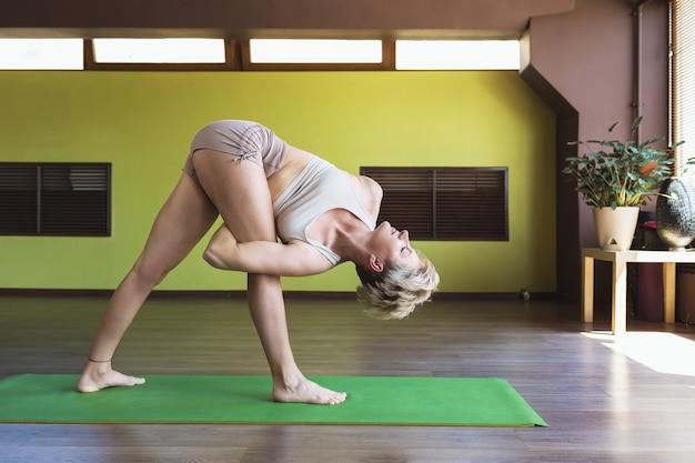ヨガを練習している女性がスタジオで三角形のポーズでトリコナサナのエクササイズを行います