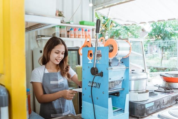 Женщина готовит прессованный напиток с помощью машины, которая была изготовлена