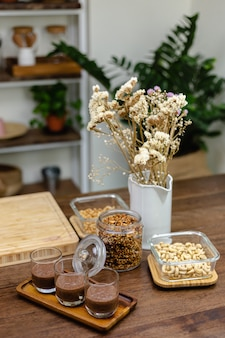 女性がキッチンでチアプリンを作り、アーモンドミルク、ココア、チアシードの最下層をレイアウトします。