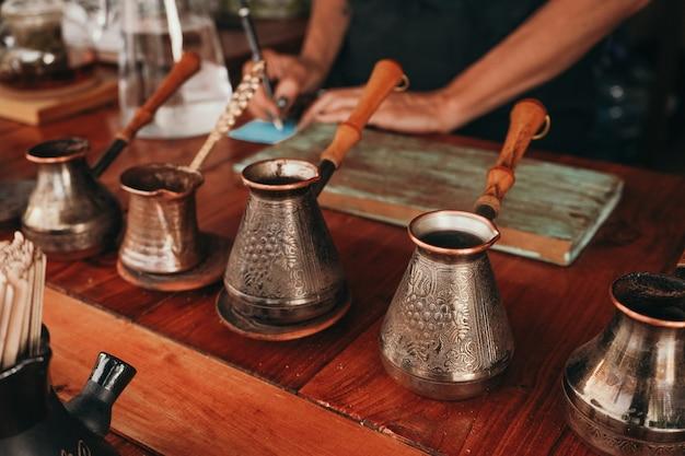 女性が砂の上でコーヒーを準備します。トルコ語でコーヒーを作るクローズアップ。伝統的な雰囲気のコーヒーショップ。