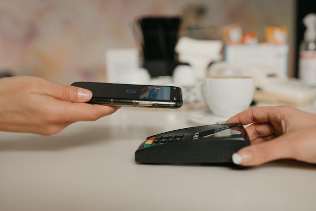 カフェで非接触型nfcテクノロジーを使用してスマートフォンでラテの支払いをする準備をしている女性。女性のバリスタがコーヒーショップのクライアントに支払うための端末を差し出します。