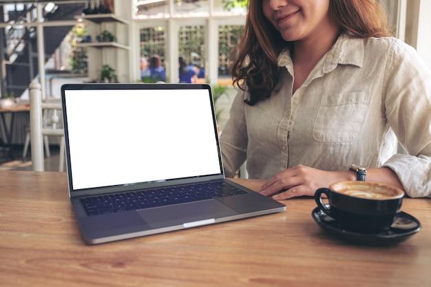 나무 테이블에 빈 흰색 화면이 모형 노트북으로 작업을 제시하는 여자