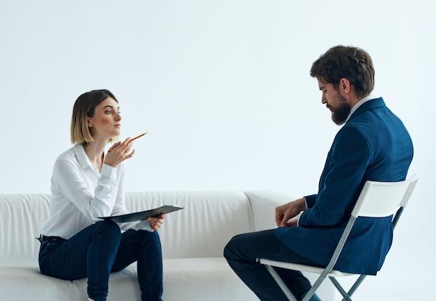 문서를 가진 여성 심리학자는 소파와 남자에 앉아있다. 고품질 사진