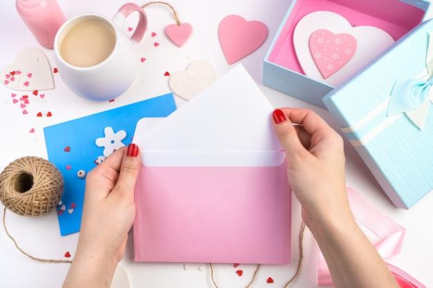 Женщина достает письмо из розового конверта на романтическом фоне с сердечками.