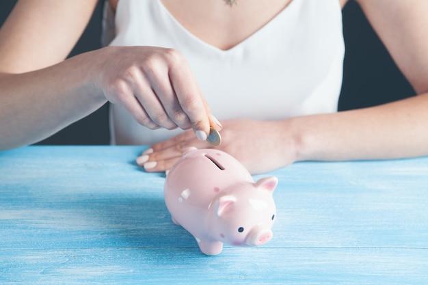 여자는 돼지 저금통에 동전을 넣어