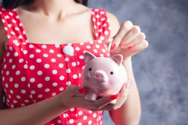 여자는 돼지 저금통에 달러 지폐를 넣어