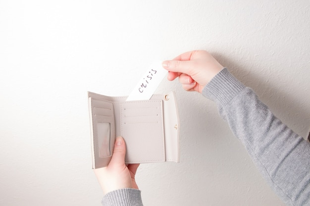 Женщина кладет в кошелек бумагу с надписью кризис