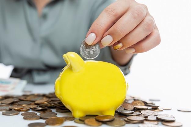 Женщина кладет русскую монету в желтую копилку. инвестирование и сбережения. крупный план.