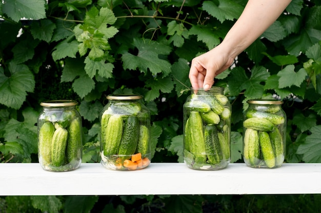 한 여성이 매리네이드에 야채를 보관하기 위해 항아리에 오이를 넣습니다.