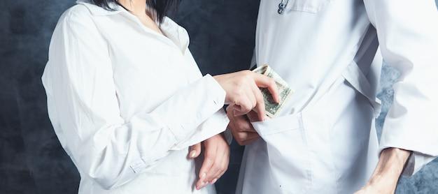 여자는 의사의 주머니에 돈을 넣습니다