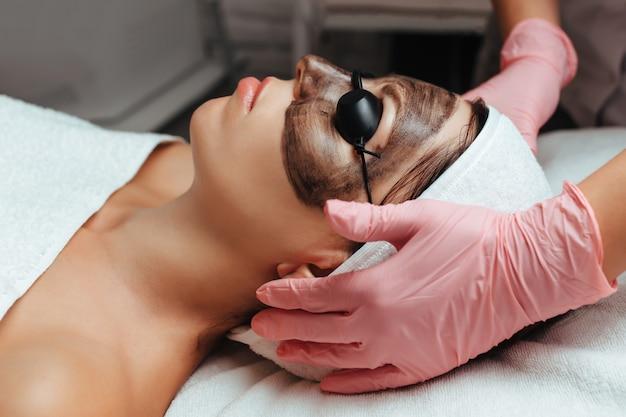 Женщина надевает очки на приеме к косметологу, чтобы сделать карбоновый пилинг.