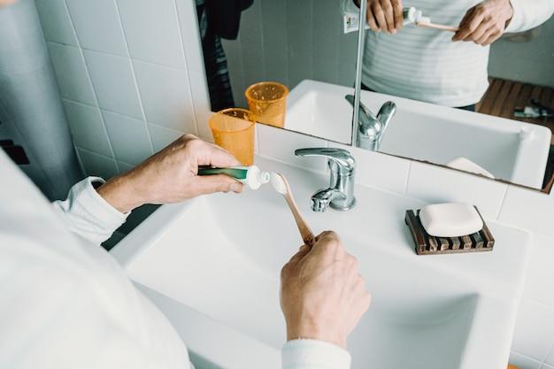 Женщина наносит крем для зубов на его бамбуковую зубную щетку