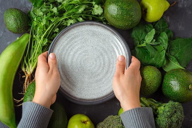 녹색 채소의 전체 테이블에 접시를 넣어 여자. 건강 식품 개념
