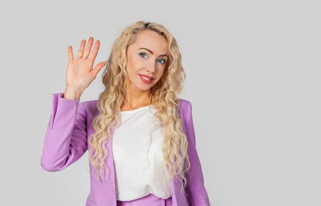女性が挨拶で手を上げ、手を上げてあなたに手を振る。