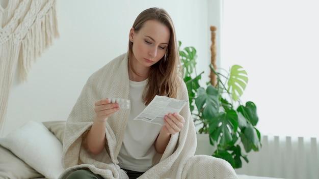 한 여성이 침실의 침대에 앉아 약을 복용하기 전에 의료 지침을 읽습니다.