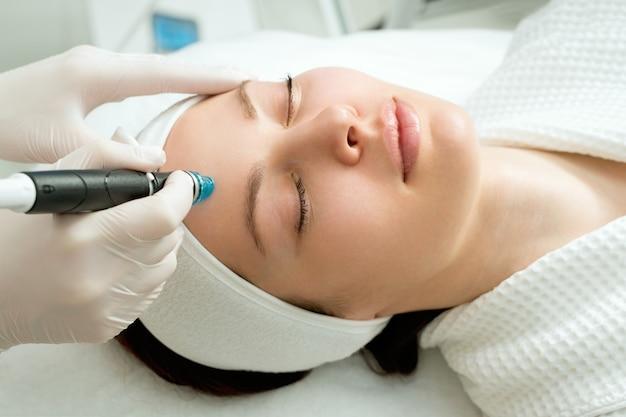 女性は美容クリニックで顔のレーザー治療を受け、肌の若返りの概念を学びます
