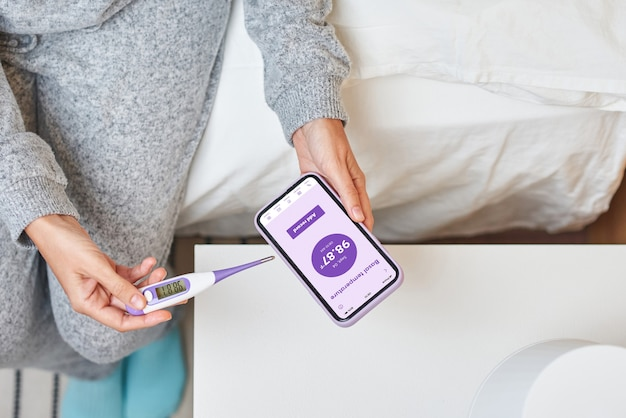 Женщина записывает базальную температуру на свой смартфон.