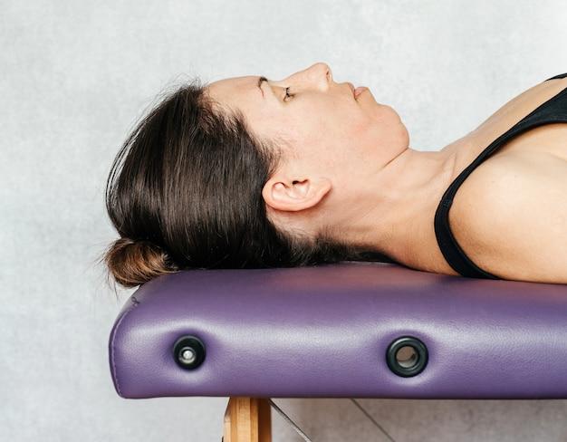 웰빙 센터의 마사지 테이블에서 휴식을 취하는 여성