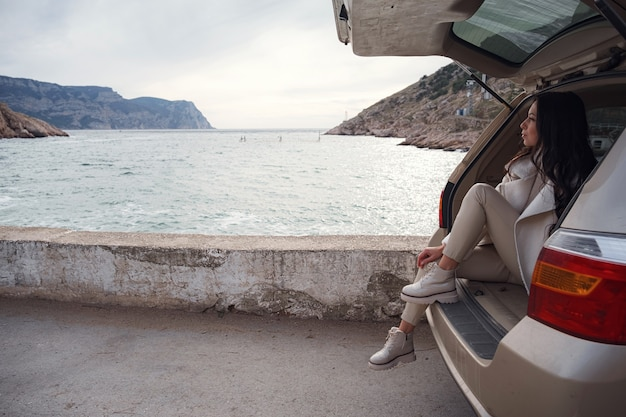 Женщина отдыхает в багажнике машины и смотрит на море. осенняя прогулка на закате. понятие свободы передвижения. осенние выходные. путешествие в одиночку или в одиночку.