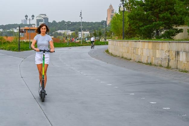 カザン堤防でスクーターに乗る女性。環境にやさしい輸送。