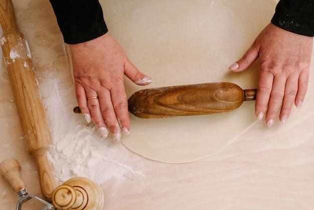 Женщина раскатывает тесто на пельмени и полуфабрикаты, запекает их темной деревянной скалкой. повар делает тесто. вид сверху