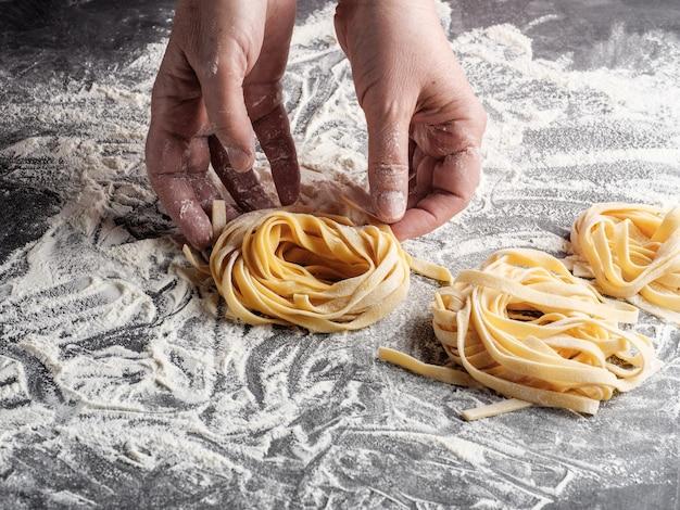 여자가 수제 이탈리아 페투치니 파스타를 굴립니다.