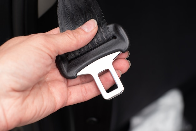 道路に乗る前に安全のために車の中に座っているときにシートベルトを締める女性の手