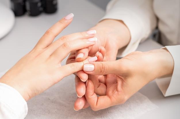 네일 살롱에서 손가락 마사지를 받고 여자의 손. 뷰티 스파에서 매니큐어 트리트먼트