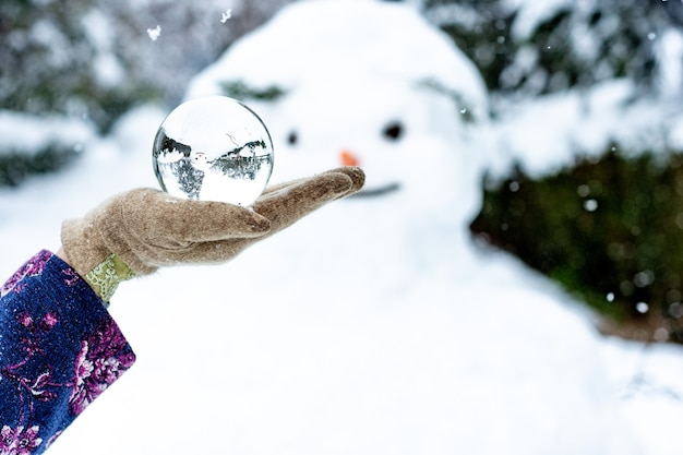 Женская рука держит хрустальный шар рядом со снеговиком.