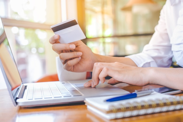 女性の手はクレジットカードを持ち、ラップトップコンピュータを使ってオンラインで買い物をする。