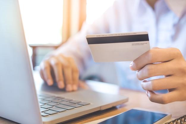 女性の手はクレジットカードを持ち、ラップトップを使ってオンラインで買い物をする