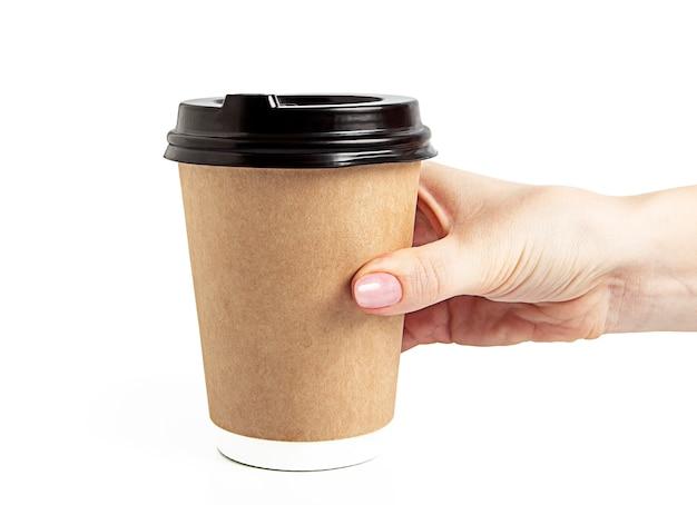 Женская рука держит одноразовую картонную кофейную чашку. изоляция на белой изолированной поверхности