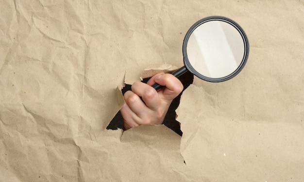 여성의 손이 유리 돋보기를 들고 있으며, 신체 일부가 갈색 종이의 구멍에서 튀어 나와 있습니다. 솔루션 검색 개념, 연구