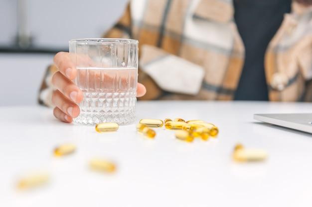 Женская рука держит стакан воды, а рядом лежат желтые таблетки.