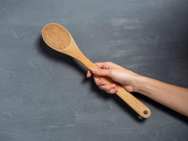 한 여성의 손이 회색 질감의 배경에 큰 나무 숟가락을 들고 있습니다. 음식을 요리하는 도구.