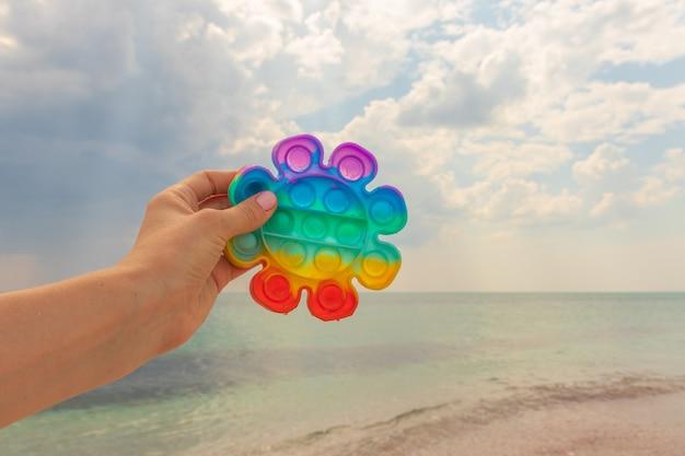 더운 화창한 날 바다를 배경으로 한 여성의 손이 팝 잇 안티 스트레스 장난감을 들고 있다