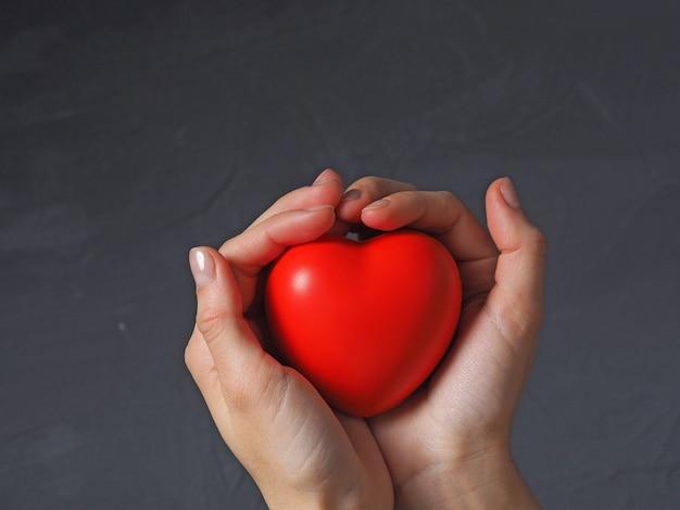 한 여성의 손이 손가락으로 회색 배경에 빨간 하트를 들고 있습니다. 건강, 사랑, 발렌타인 데이의 콘서트