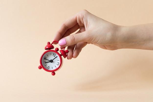 여자의 손은 베이지 색 배경에 빨간색 작은 알람 시계를 보유하고 있습니다. 고품질 사진