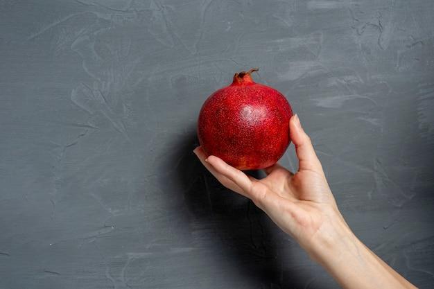 女性の手は灰色の背景に熟したジューシーなザクロの果実全体を持っています。健康的で美味しい果物。コピースペース、テキストスペース