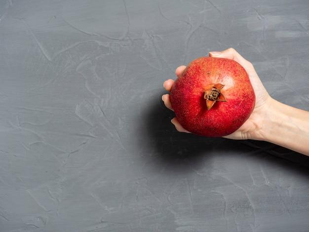 女性の手は灰色の背景に熟したジューシーなザクロの果実全体を持っています。健康的で美味しい果物。縦の写真
