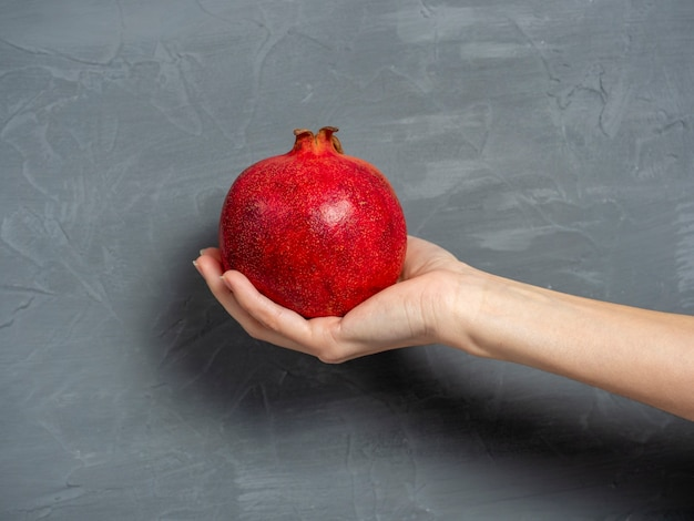 女性の手は灰色の壁に熟したジューシーなザクロの果実全体を持っています。健康的で美味しい果物。