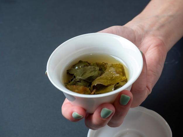 女性の手は暗い背景に淹れた緑茶と白い磁器のボウルを持っています