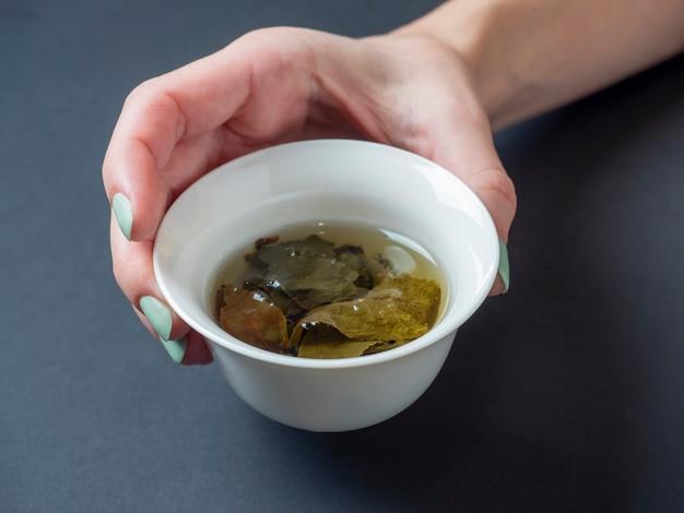 女性の手はお茶と白い磁器のボウルを持っています。暗い背景。大葉茶の開いた葉。チャイニーズティー。お茶会