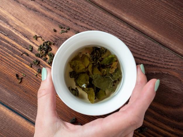 女性の手はお茶と白い磁器のボウルを持っています。木製の背景。大葉茶の開いた葉。チャイニーズティー。お茶会。上面図、フラットレイ