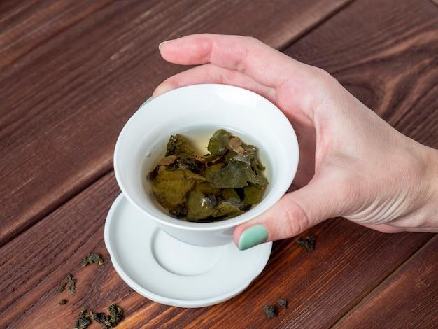 女性の手はお茶と白い磁器のボウルを持っています。木製の背景。大葉茶の開いた葉。チャイニーズティー。お茶会